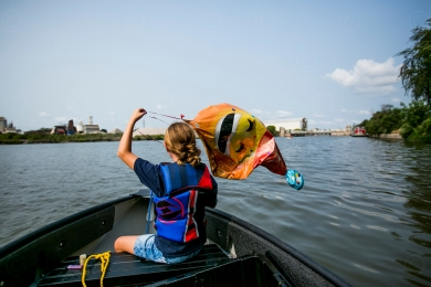 Jessica Speiss plays with a balloon she plucked out of the waters near Zug Island during a Trash Fishing outing on the Detroit River on August 8, 2018. Birmingham, MI, resident Tom Nardone and his son Mark are trying to start a Trash Fishing movement to encourage boaters to collect trash from neglected waterways.